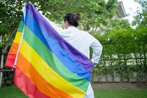 Asian lady holding rainbow color flag symbol of LGBT pride month celebrate annual in June social of gay lesbian bisexual transgender human rights photo