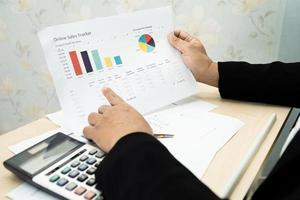 Asian accountant working and analyzing financial reports project accounting with chart graph and calculator in modern office photo