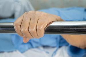 Asian senior or elderly old woman patient lie down handle the rail bed with hope on a bed in the hospital photo