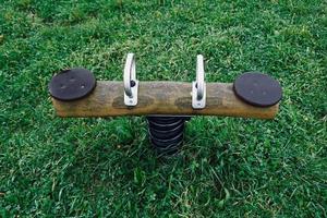 balancín de madera antiguo en el patio de recreo foto