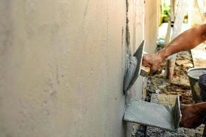 Home improvement and improvement concept Closeup of workers plastering walls to build houses photo