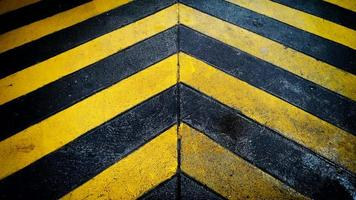 Black and yellow caution warning  patten background on the floor photo