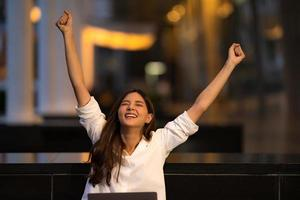 Young asian woman with happy screaming surprised face using laptop in a city photo
