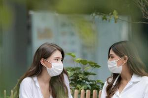 Happy two young woman with smiley face wearing face mask protective talking and laughing photo