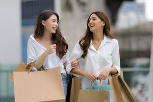 Happy friends shopping  Two young female are holding shopping bags photo