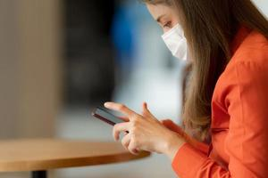 Portrait of young woman wearing face mask protective using a phone sitting near window in cafe photo