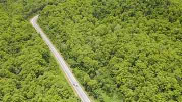Aerial top view car driving through the forest on country road view from drone photo