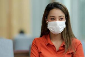 Portrait of young woman wearing face mask protective sitting in cafe photo