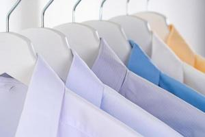 Men dress shirts Clothes on hangers on white background photo