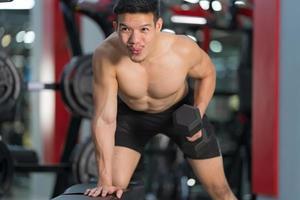 Hombre deportivo entrenando con mancuernas en el gimnasio foto