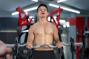 Hombre deportivo entrenando con una barra pesada en el gimnasio. foto