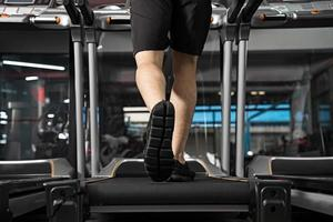 Close up of male legs running on treadmill in gym photo