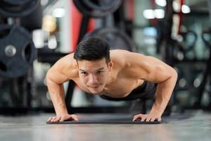 Hombre deportivo entrenamiento haciendo flexiones en el gimnasio. foto