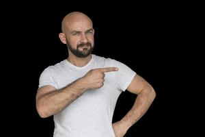 white bald man with a beard in a white t shirt points finger to the side photo