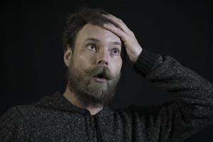 Hombre barbudo con bigote con emociones en su rostro un trabajador carpintero mano de obra foto