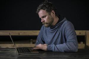 hipster bigote con barba trabaja en la computadora foto