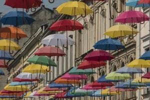sombrillas de colores cuelgan en el fondo de la ciudad vieja de lviv foto