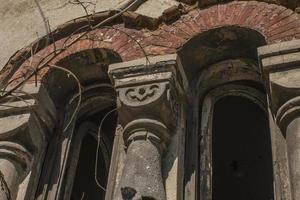 An ancient arched window destroyed by time photo