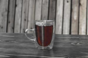 Taza de vidrio con té en una mesa de madera foto