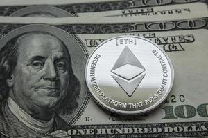 Crypto currency ethereum on the background of the dollars photo