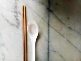 spoon and chopsticks on top of white marble background photo