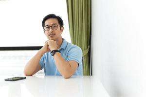 Portrait of asian man wearing eyeglass sitting at the desk and looking at camera photo