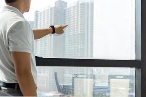 El empresario de pie delante de la ventana apunta con la mano al edificio exterior foto