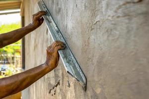 Cerca de trabajadores enyesado de paredes para construir casas foto