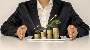 Financial growth, online merchandising, and modern business with a tree growing on coins and tablet photo