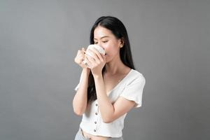 Young Asian woman with happy face and hand holding coffee cup photo