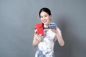 Asian woman wear Chinese traditional dress with red envelope or red packet and credit card photo