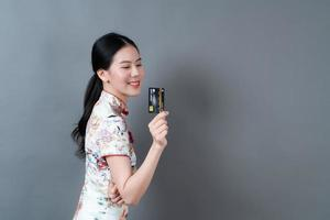 Asian woman wear Chinese traditional dress with hand holding credit card photo