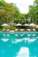 Umbrella and chair around swimming pool in hotel resort photo