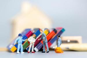 Gente en miniatura, estudiante y profesor con herramientas de papelería, concepto de regreso a la escuela foto