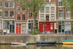 Amsterdam canal with typical dutch houses and houseboats photo