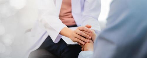 Cerrar la mano del médico psicólogo profesional asiático consultando al paciente en la habitación o en la sala de examen del hospital, concepto de salud mental foto