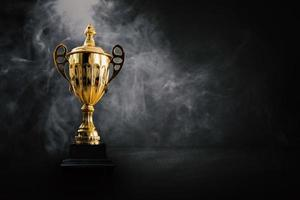 1st place champion award, the best prize and winner concept, championship cup or winner trophy in a showroom with white smoke photo