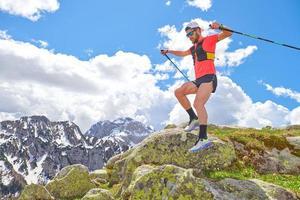 Hombre atleta salta entre las piedras durante un entrenamiento de trail en las montañas foto