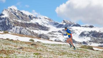 Atleta de pista en las montañas cuesta arriba con palos foto