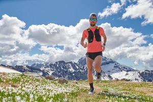 Fuerte atleta de trail running en las montañas en formación foto