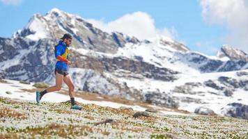 Atleta de pista en montañas cuesta abajo con palos foto