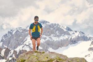 Atleta de trail running en las montañas sobre rocas foto
