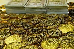 apilar monedas de oro y billetes de 100 usd foto