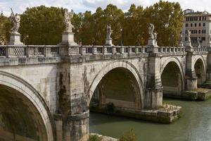 Los turistas cruzando el puente en frente del castillo de Sant Angelo en Roma Italia foto