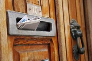 Mail box filled with rolled spam newspaper in old wooden door photo