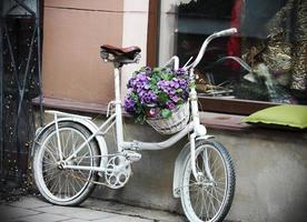 White bycicle with flower basket near shop photo