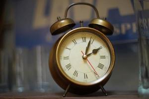 Vintage copper colored alarm clock on the cabinet shelf photo
