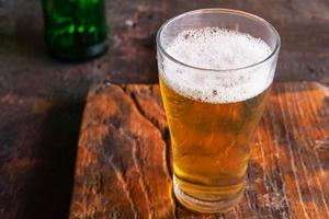 Jarras de cerveza y botellas de cerveza en una mesa de madera foto