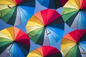 Fondo de colores de hermosas sombrillas contra el cielo azul foto