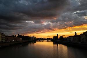 una puesta de sol en el arno de pisa foto